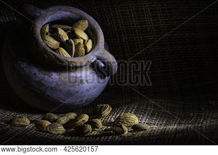 Dark Moody Food Still Life In A Rustic Style. Ripe Almond Seeds Closeup.