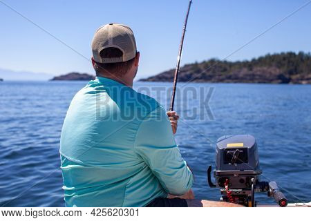 A Man Holds A Fishing Rod, Trolling For Salmon Along The Coast Of British-columbia, In A Small Zodia