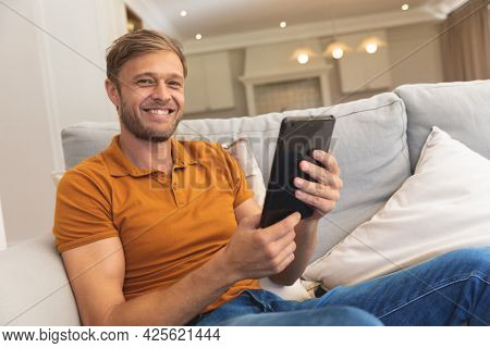 Portrait of caucasian man sitting on couch, smiling and using tablet at home. enjoying free time relaxing with technology at home.