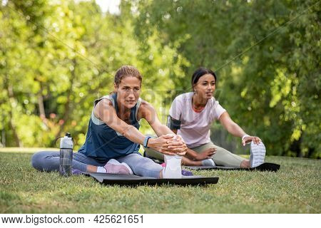 Two mature woman stretching their legs after exercise in park. Beautiful athletic woman doing stretches in the park with her mixed race friend. Sporty mid adult lady stretching after workout session.