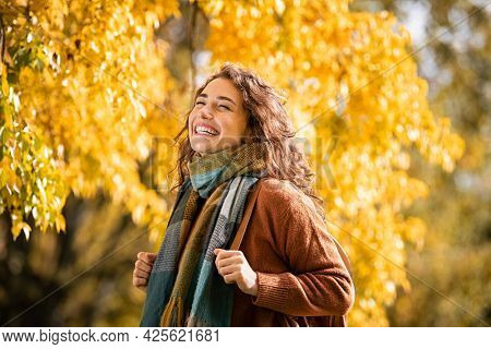 Cheerful young woman with winter scarf relaxing at park with yellow trees in background. Smiling beautiful girl enjoying warm sunny weather in autumn season. Happy pretty natural woman laughing.
