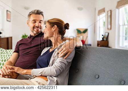 Mid adult couple embracing and relaxing on couch at home while holding hands. Romantic husband and beautiful wife hugging and looking at each other. Middle aged man relaxing at home with smiling woman
