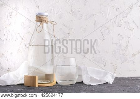 Glass Bottle With Absolutely Clean Distilled Water Isolated On Grunge Surfaces