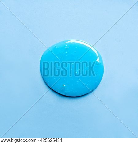 Blue Shampoo Or Shower Gel Sample Drop On Blue Background. Blue Gel Cosmetic Product With Bubbles.