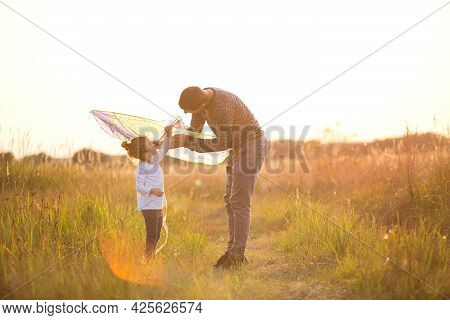 Dad Helps His Daughter To Fly A Kite In A Field In The Summer At Sunset. Family Entertainment Outdoo