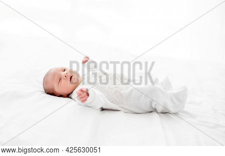 Adorable newborn baby girl wearing white costume lying in the bed and looking at the camera. Cute infant child resting at home