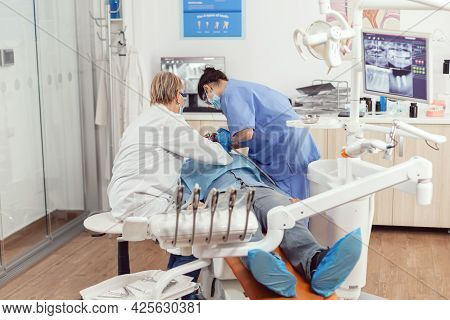 Senior Dentist Doctor And Nurse Preparing Patient For Removing Crowns. Medic Orthodontist Wearing Pr