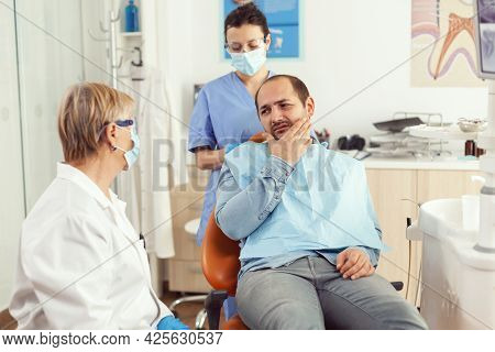 Stomatologist Doctor Talking To Man Patient With Toothache Sitting On Dental Chair Preparing For Med