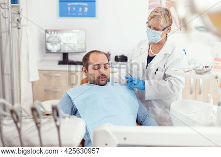 Senior Stomatologist Helping Patient To Stand Up After Dental Surgery During Medical Stomatology Cli