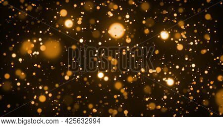 Image of glowing gold spots of light moving in hypnotic motion on brown background. Light and movement concept digitally generated image.