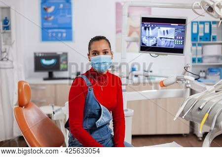Patient With Teeth Health Hygiene Issues Wearing Face Mask In Detal Clinic Looking At Camera. Woman
