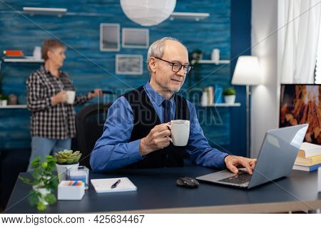 Happy Senior Man After Reading A Email With Good News Sitting At Desk. Elderly Man Entrepreneur In H