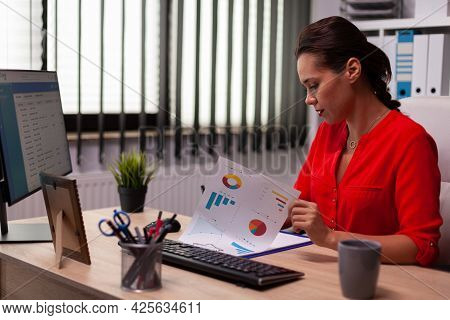 Businesswoman Entrepreneur Sitting At Desk During Professional Business Call Wearing Red. Busy Freel