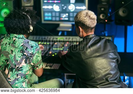 Young Audio Engineer People Having Fun Working With Mixer Sound Panel Control In Music Recording Stu