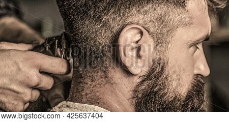 Hands Of Barber With Hair Clipper, Close Up. Haircut Concept. Hipster Client Getting Haircut. Man Vi
