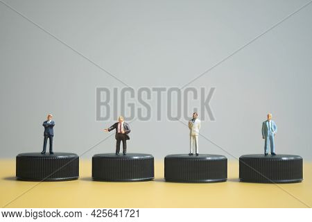 Close Up Of Miniature Businessmen In Varying Attire Standing A Row And Stand On Black Stand, As Back