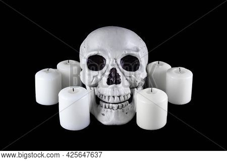 Human Skull Among White Extinguished Candles In The Dark, Scary Still Life, Altar