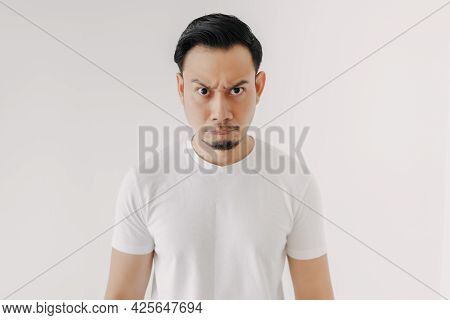 Grumpy Face Asian Man In White T-shirt Isolated On White Background.