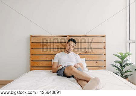 Asian Man Falls Asleep On The Bed With The Smartphone In His Hand.
