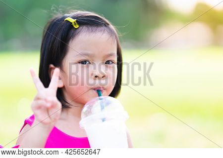 Asian Girl Sucks Fresh Coconut Milk From A Plastic Cup To Cool Off. On A Hot Day. Cute Child Held Up