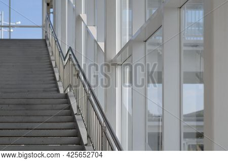 Empty Staircase In An Elevated Passage With Large Windows
