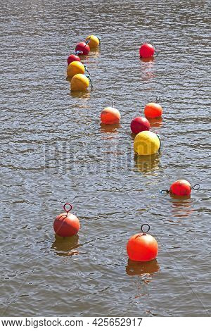 A Series Of Small Red, Yellow, And Orange Buoys On The Floating Harbour In Bristol, Uk