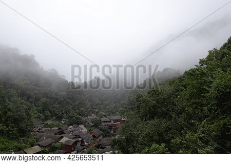 Small Village In Deep Valley Covered In Fog, Mae Kampong, Chiangmai, Thailand.