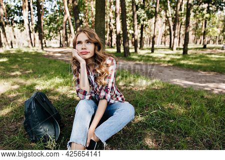 Pensive Caucasian Girl With Backpack Sitting On The Grass And Looking Up. Outdoor Portrait Of Dreamy
