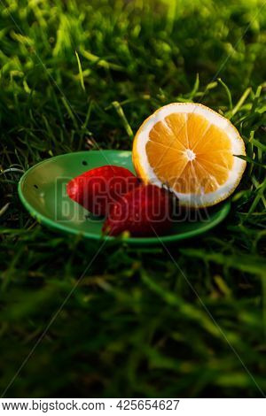 Defocus Close-up Saucer With Lemon And Two Strawberry Standing On Deep Green Grass. Blurred Nature B