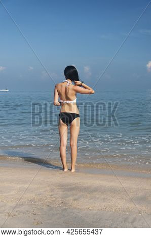 A Chinese Woman Wearing A White And Black Bikini Looking Out At A Jet Ski On The Malacca Straits At