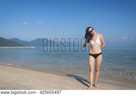 A Chinese Woman Wearing A White And Black Bikini Fixing Her Hair At Long Beacn Batu Ferringhi Penang