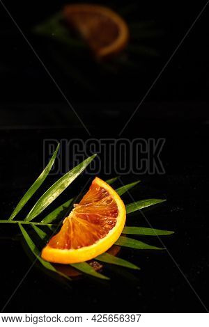 A Slice Of Red Orange Rests On A Green Palm Branch. Black Glass Background, Reflected In The Surface