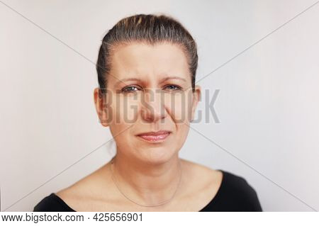 A Beautiful Woman With A Sad Irritating Face On A Gray Background With Gray Hair. She Is Sad Because