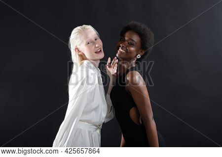 Caucasian Albino Girl And African American Young Woman Hugging On Black Background. Women Friendship