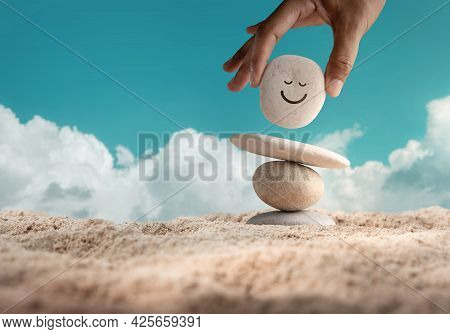 Enjoying Life Concept. Harmony And Positive Mind. Hand Setting Natural Pebble Stone With Smiling Fac