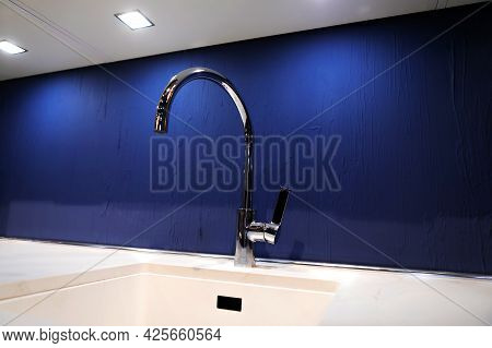 Kitchen Faucet On The Background Of A Blue Illuminated Wall. Copy Space