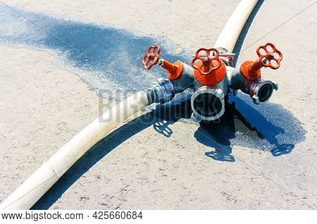 Fire Hose. Triple Valve For Connecting Hoses While Extinguishing A Fire Lying In A Puddle On The Pav