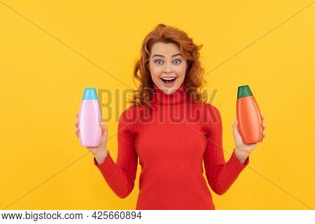 Amazed Redhead Woman Curly Dyed Hair Choosing Body Care Product Of Shampoo Bottle, Amazement
