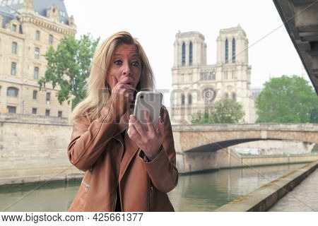 Blonde Woman On The Street, Shocked And Surprised Looking At Her Smartphone. Cathedral Notre Dame In