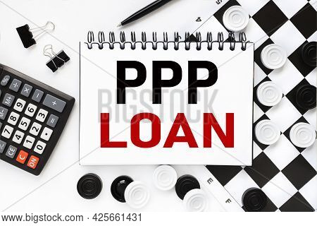 Paycheck Protection Program Ppp Loan. Notepad On A White Background Near The Chessboard, Checkers Of