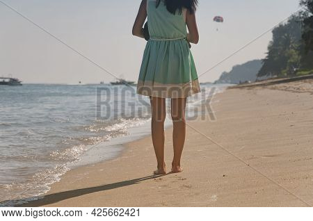 A Woman Walking On Long Beach At Batu Ferringhi On A Sunny Summer Day In Penang Malaysia.