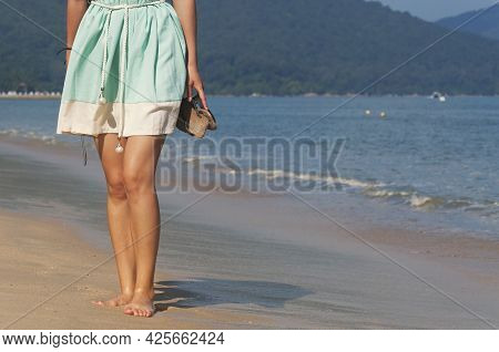 A Woman Wearing A Dress Standing On Long Beach Holding Sandals At Batu Ferringhi On A Summer Day In