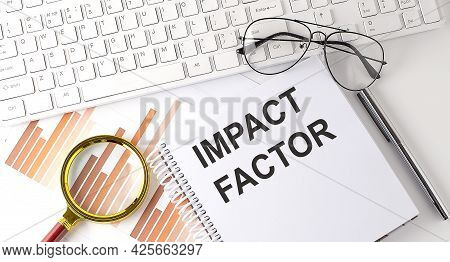 Impact Factor Text Written On Notebook With Keyboard, Chart,and Glasses