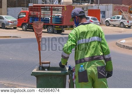 Street Cleaner, Back View To Arab Origin Man In Uniform Collecting Street Rubbish To Dumpster During