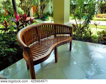 Empty Wooden Bench In Tropical Garden, Outdoor Furniture. Relax And Rest Concept. Patio Design.