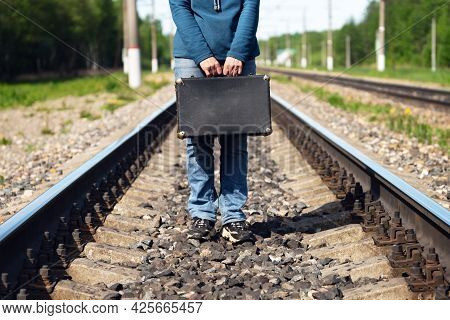 Woman Stands On The Railroad Holding In Hands An Old Suitcase In Summer Morning