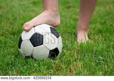 Bare Foot Of A Girl On The Soccer Ball In Green Grass