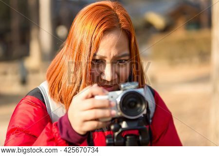 Young Woman Holding Camera In Hand. Photographer Woman With Camera Looking Photos On Camera.