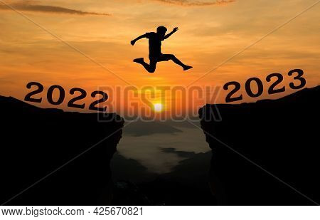 A Young Man Jump Between 2022 And 2023 Years Over The Sun And Through On The Gap Of Hill  Silhouette