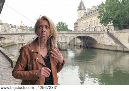 Woman With A Worried Look In The Street. Portrait Of A Mature Blonde Woman In The City Of Paris. Sai